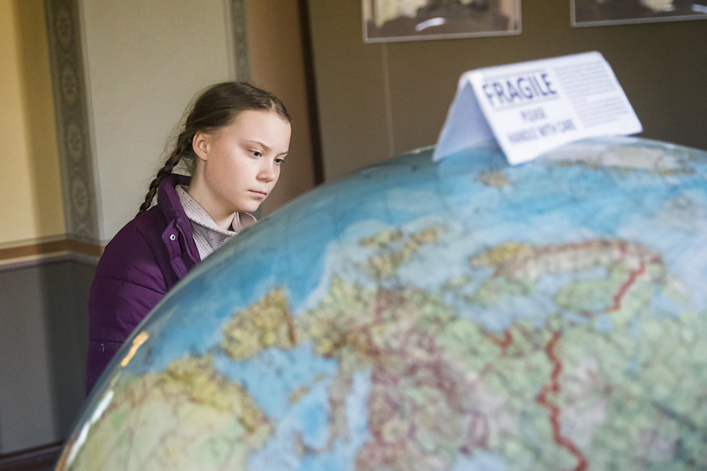 """Die schwedische Klimaaktivistin Greta Thunberg betrachtet einen Globus im Potsdam-Institut f?r Klimafolgenforschung am 29. M?rz 2019. Auf dem Modell steht ein Schild mit der Warnung """"Fragile please handle with care""""."""